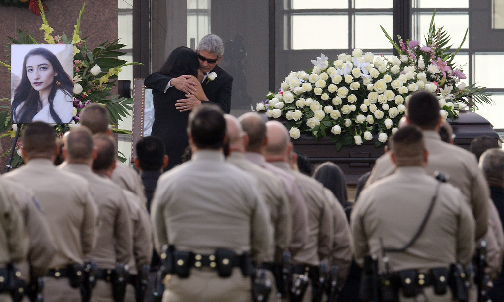 . The parents of Yvette Velasco, Robert and Marie Velasco, embrace next to the casket of their daughter Thursday December 10, 2015 during her funeral service at Forest Lawn in Covina. Velasco is the first of the 14 victims from the Dec. 2 Inland Regional Center mass shooting to be buried.  (Will Lester/Inland Valley Daily Bulletin)