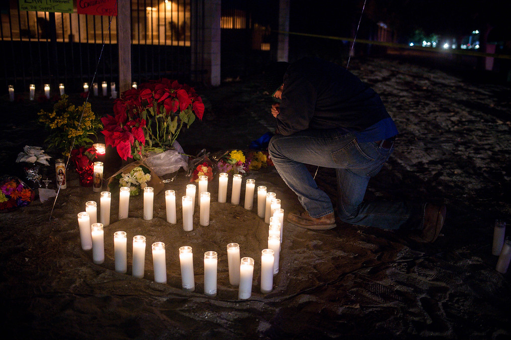 . Aaron Fierro leaves a candle at a makeshift memorial to those killed and injured in the Inland Regional Center shooting on Thursday night, December 3, 2015 in San Bernardino.  (Photo by Sarah Reingewirtz/Pasadena Star-News)
