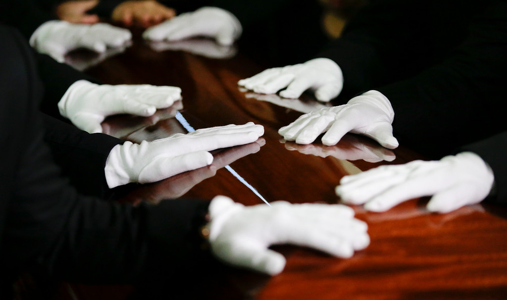 . The hand of pallbearers rest of the coffin of Tin Nguyen at her funeral on Saturday, Dec. 12, 2015, in Santa Ana, Calif. Nguyen died in the mass shootings in San Bernardino, Calif., on Dec. 2. (AP Photo/Chris Carlson)