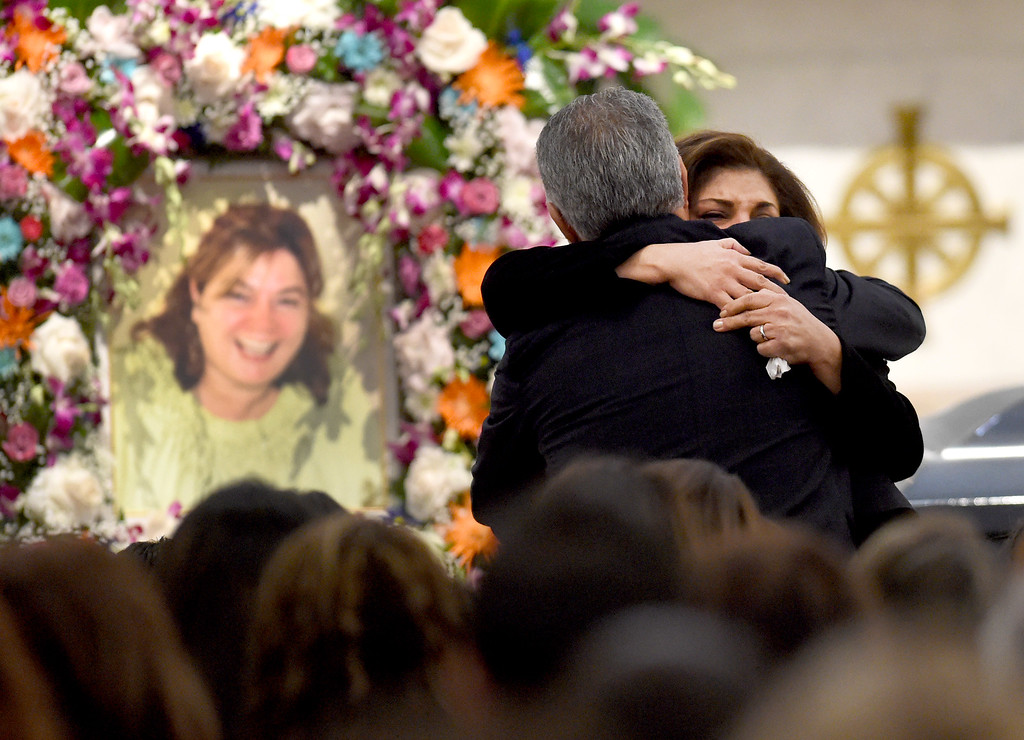 . Domarina Awdow hugs her cousin Arlen Verdehyou, husband of Bennetta Bet-Babal, after giving the eulogy for Bet-Badal\'s funeral service, at Sacred Heart Catholic Church Rancho Cucamonga, Ca. Monday, December 14, 2015. Bet-Badal was one of fourteen killed in the December 2, mass shooting at the Inland Regional Center in San Bernardino. (Photo by John Valenzuela/The Sun)