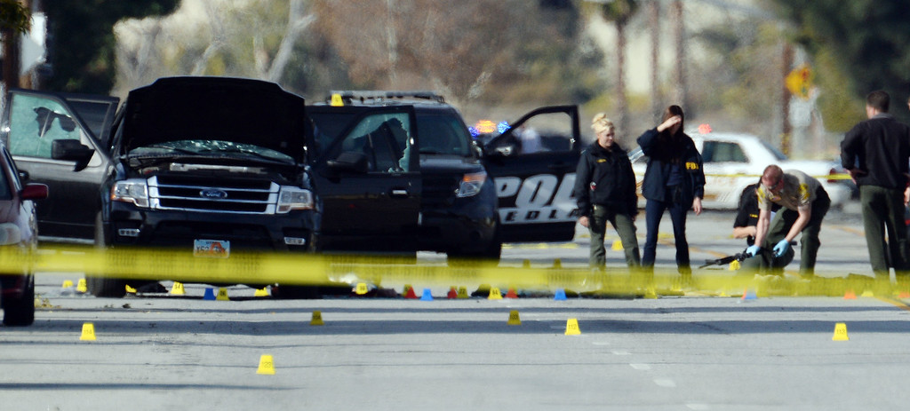 . A law enforcement officer (second from right) appears to pick up a long gun off the ground as they investigate the scene on San Bernardino Avenue Thursday morning December 3, 2015 following a police gun battle Wednesday which ended with the killing of a male and female who were possibly involved in the mass shooting which killed 14 people at the Inland Regional Center in San Bernardino Wednesday morning.  (Will Lester/Inland Valley Daily Bulletin)