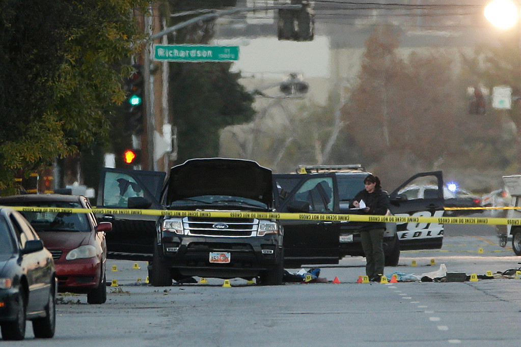 . An investigator looks at a Black SUV that was involved in a police shootout with suspects, Thursday, Dec. 3, 2015, in San Bernardino, Calif.  A heavily armed man and woman opened fire Wednesday on a holiday banquet, killing multiple people and seriously wounding others in a precision assault, authorities said. Hours later, they died in a shootout with police.  (AP Photo/Jae C. Hong)