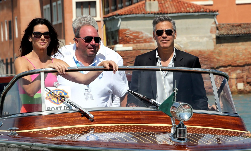 """. George Clooney (R) steers a boat next tactress Sandra Bullock before the photocall of the movie \""""Gravity\"""" presented out of competition on the opening day of the 70th Venice Film Festival on August 28, 2013 at Venice Lido.        (TIZIANA FABI/AFP/Getty Images)"""