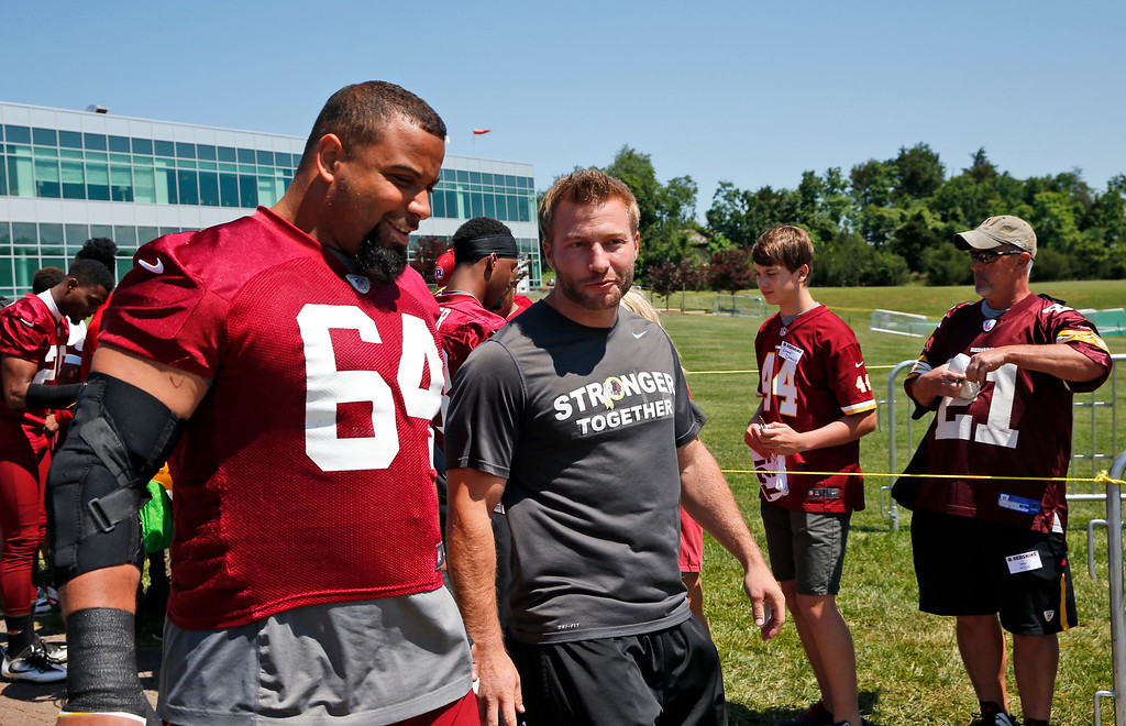 . Washington Redskins nose tackle Kedric Golston (64) and offensive coordinator Sean McVay talk as they walk to practice at the team\'s NFL football training facility at Redskins Park, Wednesday, June 8, 2016 in Ashburn, Va. (AP Photo/Alex Brandon)
