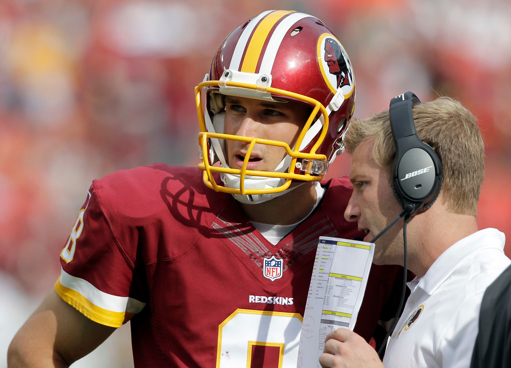 . Washington Redskins quarterback Kirk Cousins (8) listens to offensive coordinator Sean McVay, during the second half of an NFL football game against the Jacksonville Jaguars Sunday, Sept. 14, 2014, in Landover, Md. The Redskins won 41-10. (AP Photo/Mark E. Tenally)