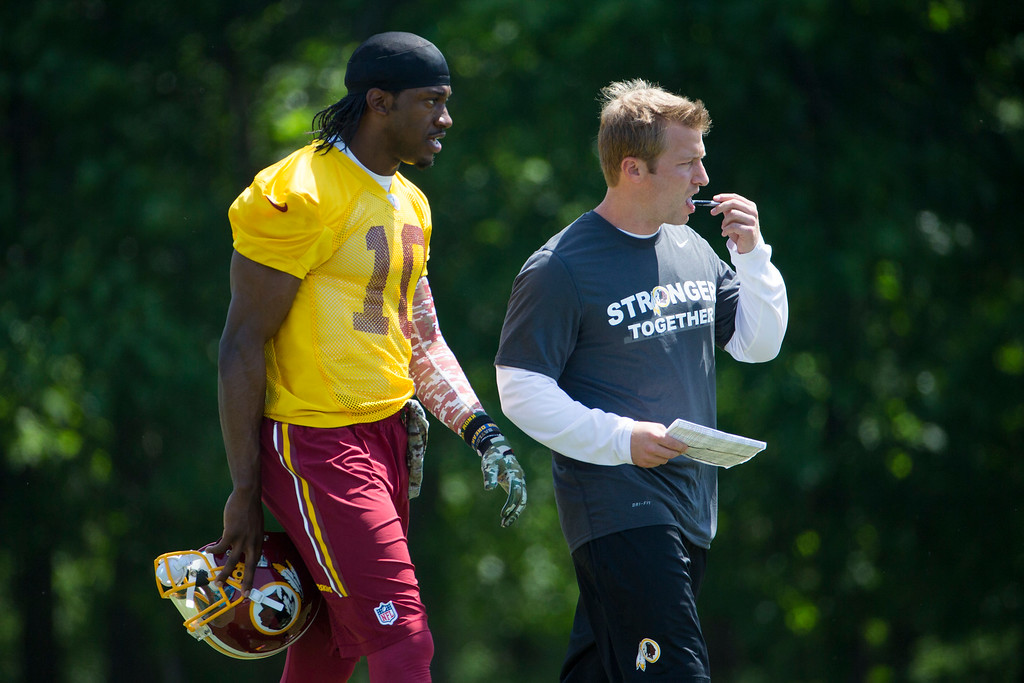 . Washington Redskins offensive coordinator Sean McVay, right, walks with quarterback Robert Griffin III during an NFL football organized team activity at Redskins Park, on Tuesday, May 26, 2015, in Ashburn, Va. (AP Photo/Evan Vucci)