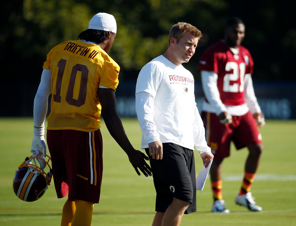 . Washington Redskins quarterback Robert Griffin III and offensive coordinator Sean McVay talk during practice at the team\'s NFL football training facility, Friday, July 25, 2014 in Richmond, Va. (AP Photo)