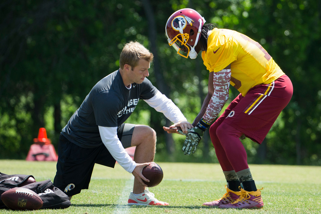 . Washington Redskins offensive coordinator Sean McVay, left, works with quarterback Robert Griffin III during an NFL football organized team activity at Redskins Park, on Tuesday, May 26, 2015, in Ashburn, Va. (AP Photo/Evan Vucci)