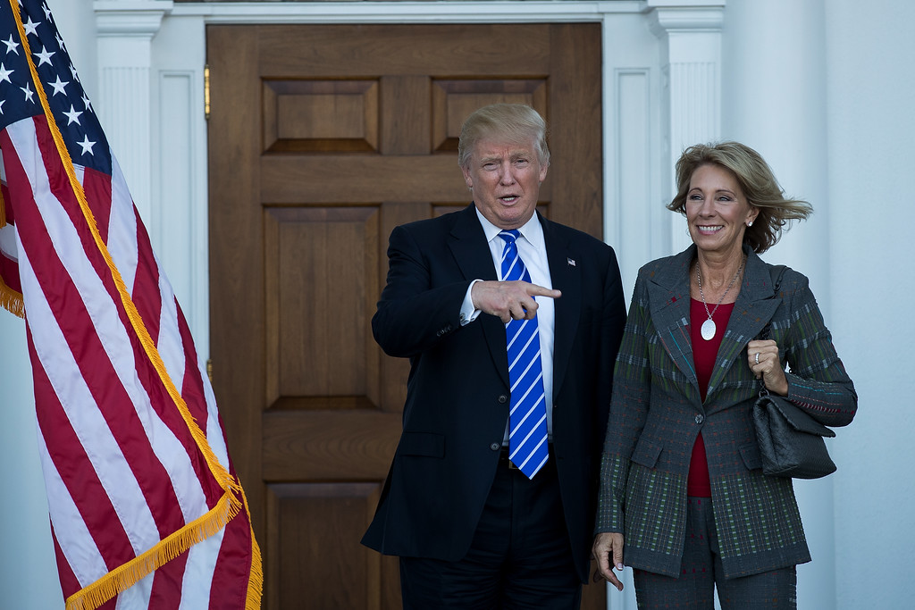 . BEDMINSTER TOWNSHIP, NJ - NOVEMBER 19: (L to R) president-elect Donald Trump and Betsy DeVos  pose for a photo after their meeting at Trump International Golf Club, November 19, 2016 in Bedminster Township, New Jersey. Trump and his transition team are in the process of filling cabinet and other high level positions for the new administration.  (Photo by Drew Angerer/Getty Images)
