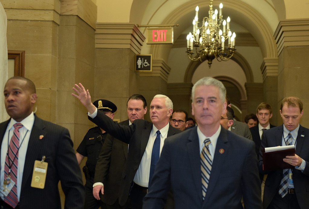 . Vice President Mike Pence waves as he is escorted by Senate Sergeant-at-Arms Frank J. Larkin, front right, on Capitol Hill in Washington, Tuesday, Feb. 7, 2017, after casting the tie-breaking vote for Education Secretary Betsy DeVos. (AP Photo/Susan Walsh)