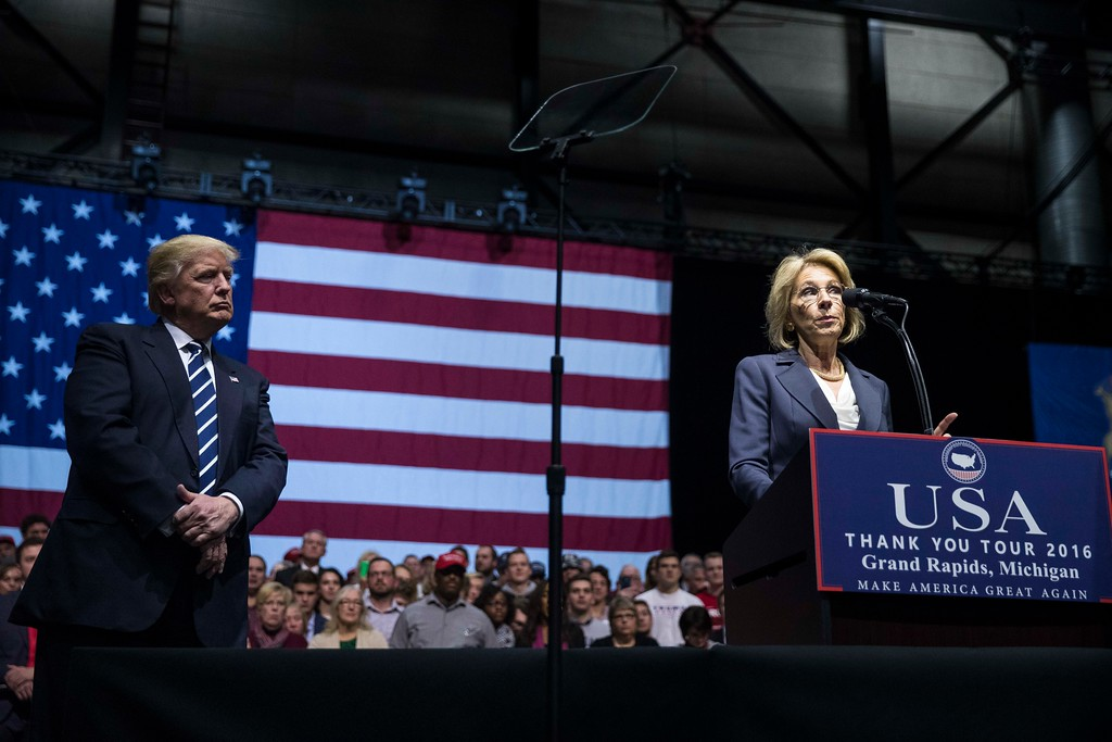 . GRAND RAPIDS, MI - DECEMBER 9: (L to R) President-elect Donald Trump looks on as Betsy DeVos, his nominee for Secretary of Education, speaks at the DeltaPlex Arena, December 9, 2016 in Grand Rapids, Michigan. President-elect Donald Trump is continuing his victory tour across the country. (Photo by Drew Angerer/Getty Images)