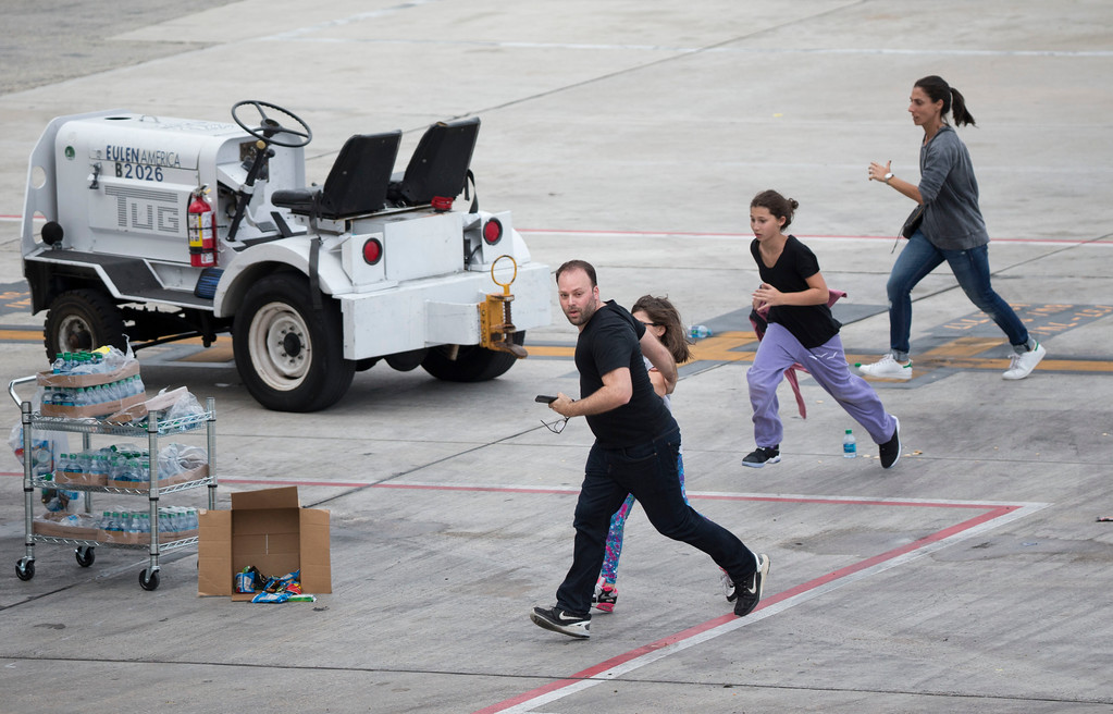 . People run on the tarmac at Fort Lauderdale�Hollywood International Airport, Friday, Jan. 6, 2017, in Fort Lauderdale, Fla., after a shooter opened fire inside a terminal of the airport, killing several people and wounding others before being taken into custody. (AP Photo/Wilfredo Lee)