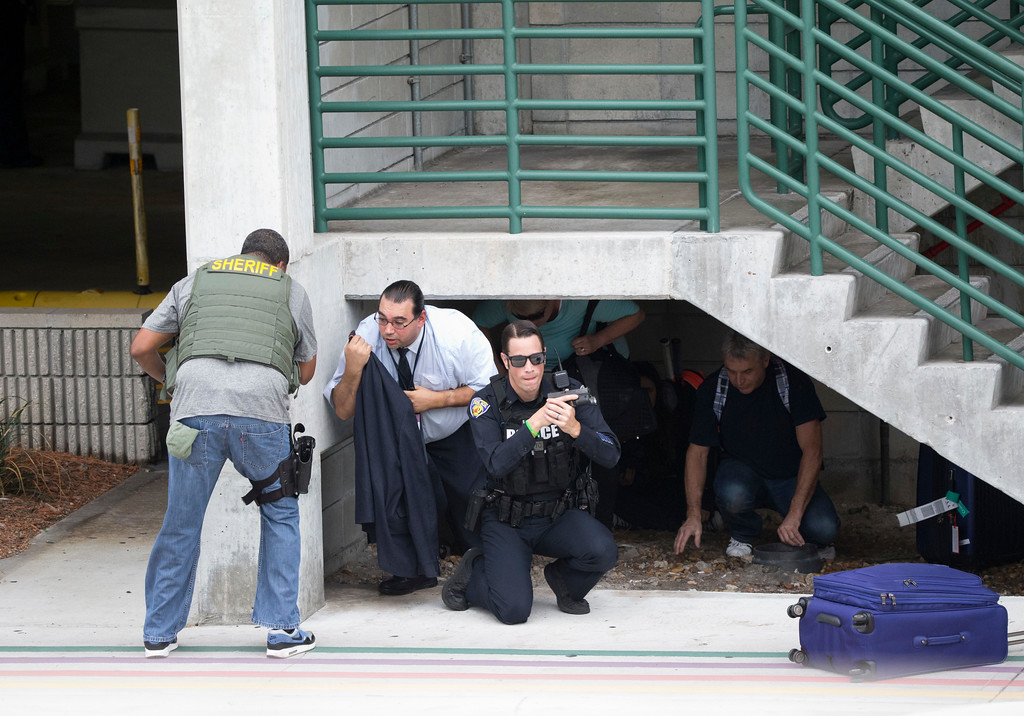 . Law enforcement personnel shield civilians outside a garage area at Fort Lauderdale�Hollywood International Airport, Friday, Jan. 6, 2017, in Fort Lauderdale, Fla., after a shooter opened fire inside a terminal of the airport, killing several people and wounding others before being taken into custody. (AP Photo/Wilfredo Lee)