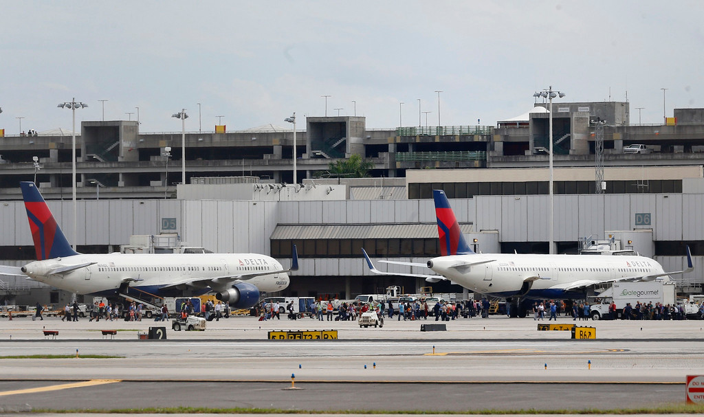 . People stand on the tarmac at the Fort Lauderdale-Hollywood International Airport after a shooter opened fire inside a terminal of the airport, killing several people and wounding others before being taken into custody, Friday, Jan. 6, 2017, in Fort Lauderdale, Fla. (Al Diaz /Miami Herald via AP)