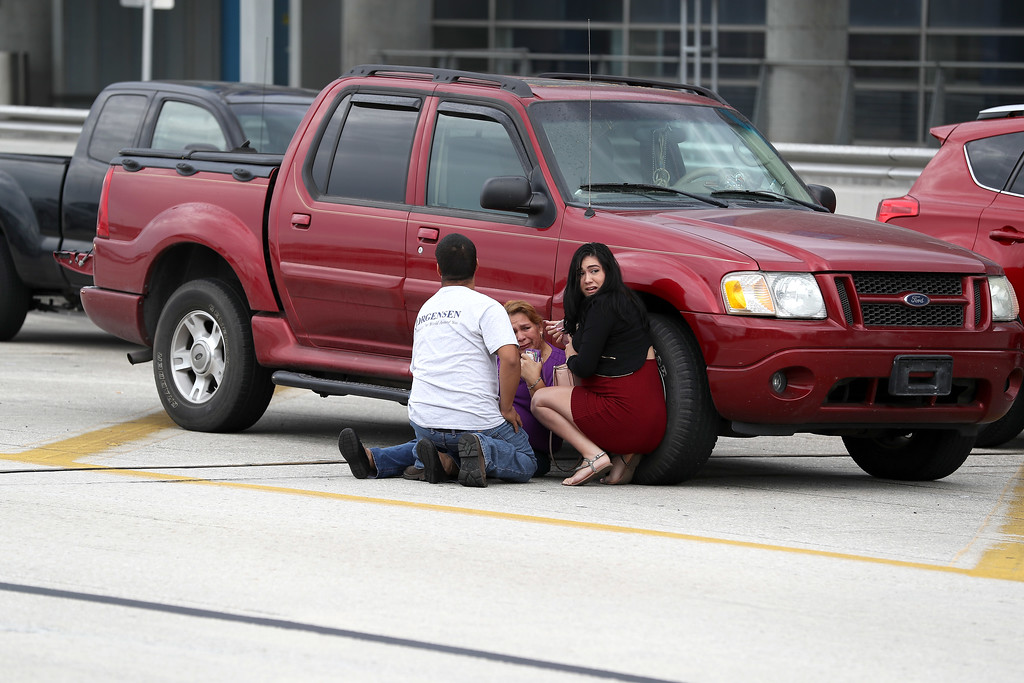 . FORT LAUDERDALE, FL - JANUARY 06:  People take cover outside the Fort Lauderdale-Hollywood International airport after a shooting took place near the baggage claim on January 6, 2017 in Fort Lauderdale, Florida. Officials are reporting that five people wear killed and 8 wounded in an attack by a single gunman.   (Photo by Joe Raedle/Getty Images)