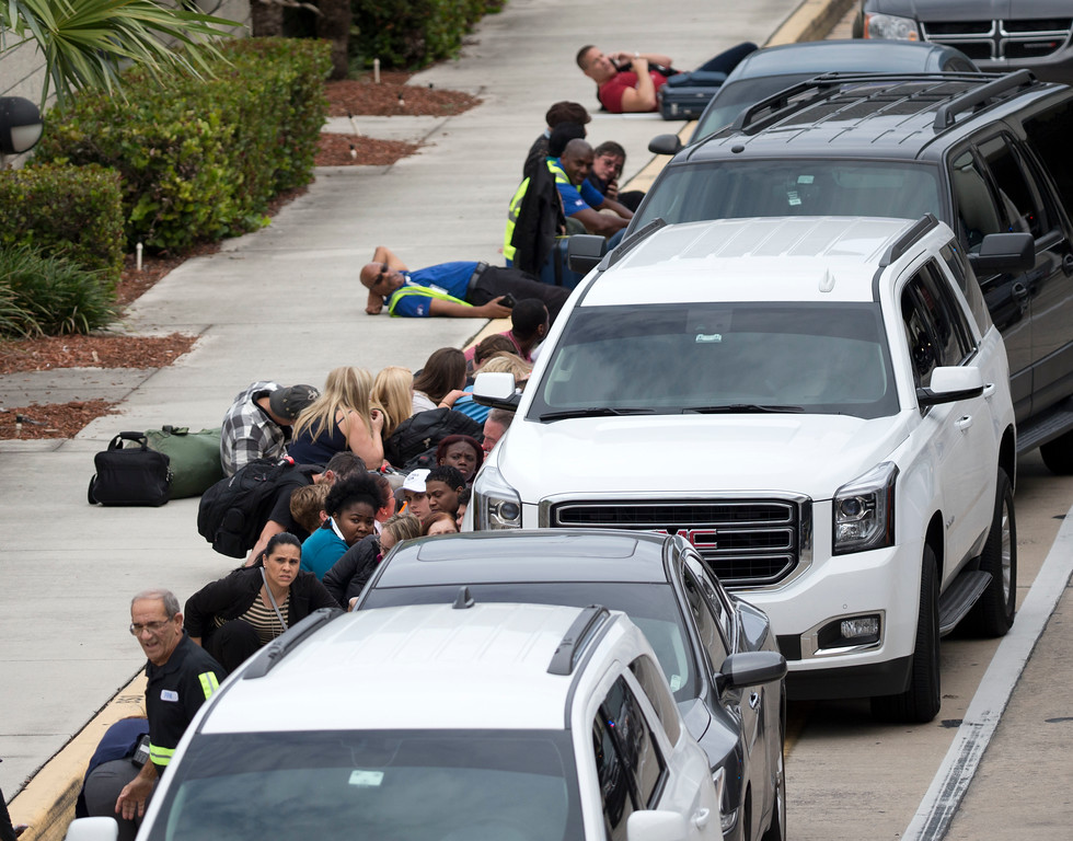 . People take cover outside Fort Lauderdale�Hollywood International Airport, Friday, Jan. 6, 2017, in Fort Lauderdale, Fla., after a shooter opened fire inside a terminal of the airport, killing several people and wounding others before being taken into custody.  (AP Photo/Wilfredo Lee)