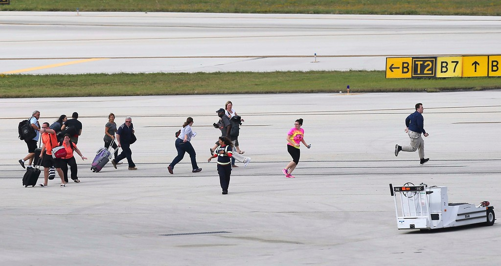 . Passengers run on the tarmac at Fort Lauderdale-Hollywood International Airport, Friday, Jan. 6, 2017, in Fort Lauderdale, Fla.   A gunman opened fire in the baggage claim area at the airport Friday, killing several people and wounding others before being taken into custody in an attack that sent panicked passengers running out of the terminal and onto the tarmac, authorities said. (David Santiago/El Nuevo Herald via AP)