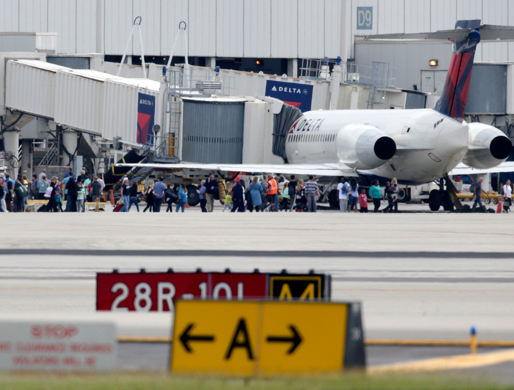 . People stand on the tarmac at the Fort Lauderdale-Hollywood International Airport after a shooter opened fire inside the terminal, killing several people and wounding others before being taken into custody, Friday, Jan. 6, 2017, in Fort Lauderdale, Fla. (AP Photo/Lynne Sladky)