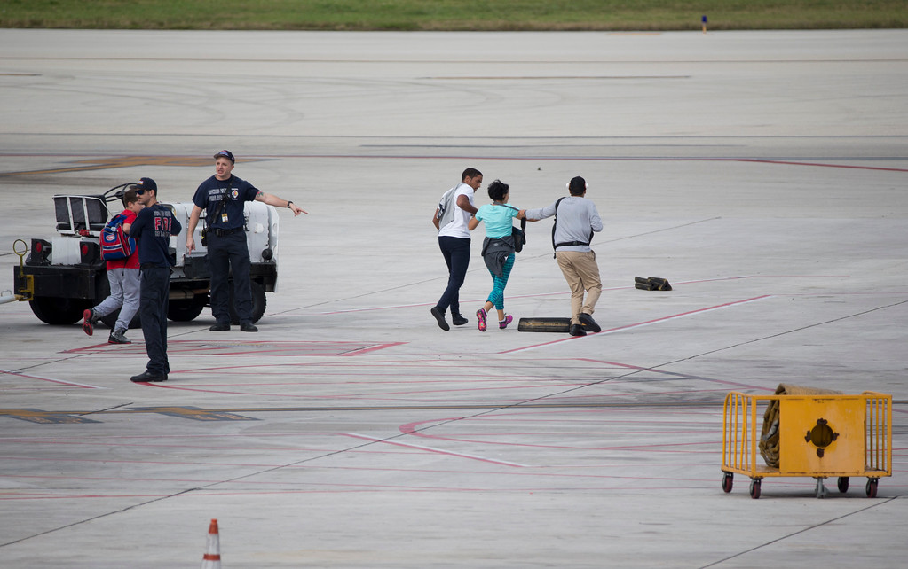. People run out onto the tarmac at Fort Lauderdale�Hollywood International Airport, after a gunman opened fire in the baggage claim area at the airport killing several people and wounding others before being taken into custody Friday, Jan. 6, 2017, in Fort Lauderdale, Fla. (AP Photo/Wilfredo Lee)