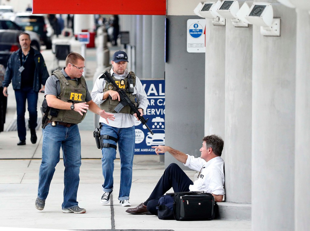 . A law enforcement officers talk to a man at Fort Lauderdale�Hollywood International Airport, Friday, Jan. 6, 2017, in Fort Lauderdale, Fla.   A gunman opened fire in the baggage claim area at the airport Friday, killing several people and wounding others before being taken into custody in an attack that sent panicked passengers running out of the terminal and onto the tarmac, authorities said. (AP Photo/Wilfredo Lee)