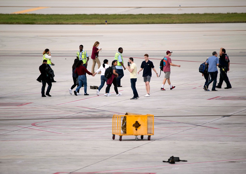 . People are shown on the tarmac at Fort Lauderdale�Hollywood International Airport, Friday, Jan. 6, 2017, in Fort Lauderdale, Fla. A gunman opened fire in the baggage claim area at the airport Friday, killing several people and wounding others before being taken into custody in an attack that sent panicked passengers running out of the terminal and onto the tarmac, authorities said. (AP Photo/Wilfredo Lee)