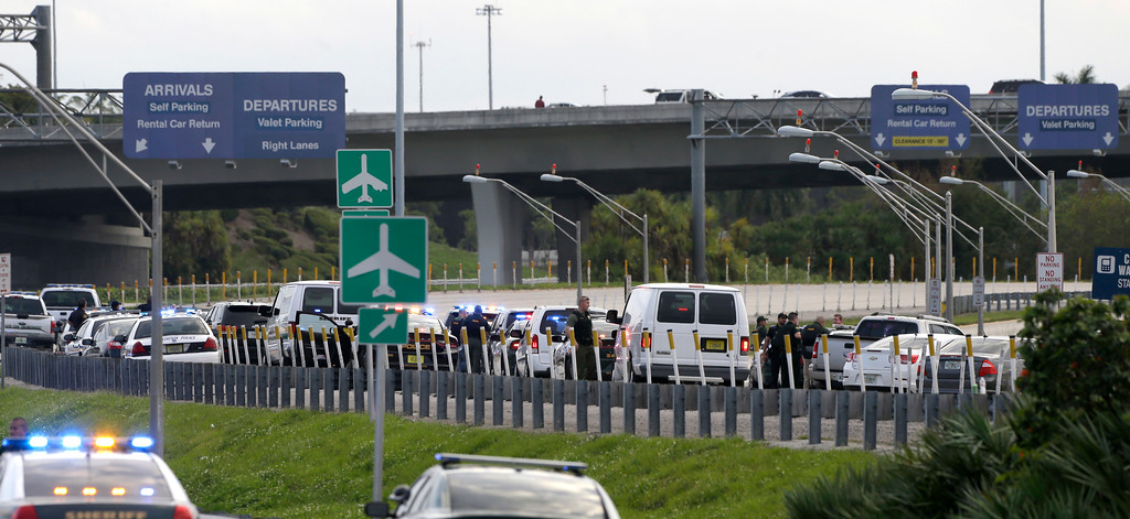 . Law enforcement officers block on of the entrances to Fort Lauderdale-Hollywood International Airport, Friday, Jan. 6, 2017, in Fort Lauderdale, Fla. A lone shooter opened fire at the Fort Lauderdale, Florida, international airport Friday, killing five people and injuring eight before he was taken into custody, officials said. The airport suspended operations as law enforcement authorities rushed to the scene and emergency medical workers treated at least one bleeding victim on the tarmac. (AP Photo/Alan Diaz)