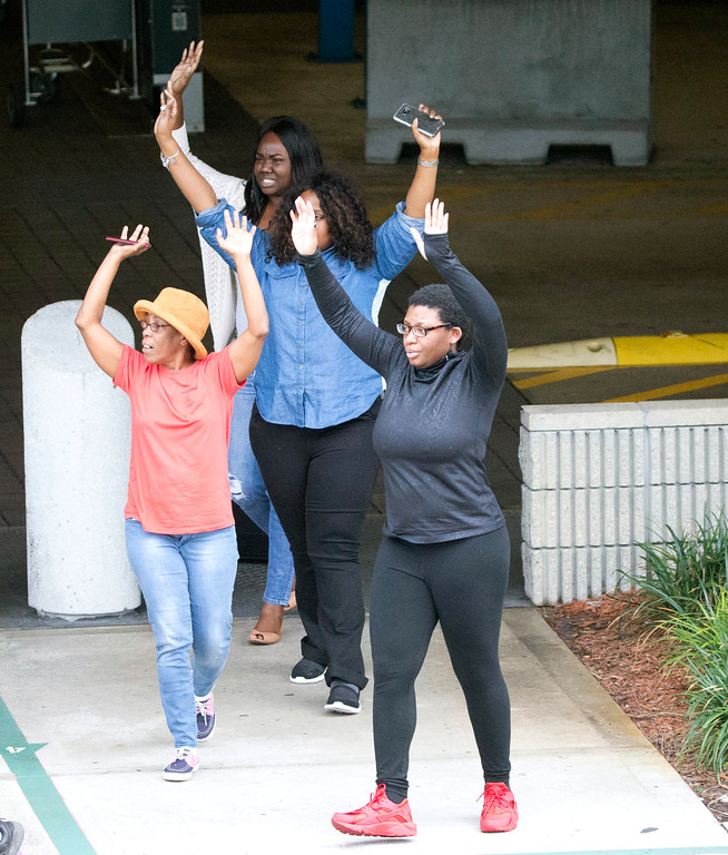 . People leave a garage area with their hands up in the air outside Fort Lauderdale�Hollywood International Airport, after a shooter opened fire inside a terminal of the airport, killing several people and wounding others before being taken into custody, Friday, Jan. 6, 2017, in Fort Lauderdale, Fla. (AP Photo/Wilfredo Lee)