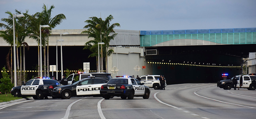 . Authorities close the entrance to Fort Lauderdale International Airport along U.S. 1 following a shooting at Terminal 2, Friday, Jan. 6, 2017.  A gunman opened fire in the baggage claim area at the airport Friday, killing several people and wounding others before being taken into custody in an attack that sent panicked passengers running out of the terminal and onto the tarmac, authorities said. (Jim Rassol/South Florida Sun-Sentinel via AP)