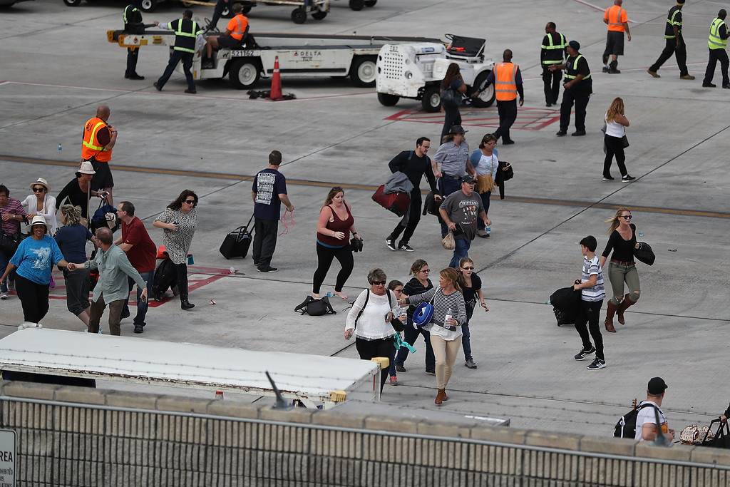 . FORT LAUDERDALE, FL - JANUARY 06: People seek cover on the tarmac of Fort Lauderdale-Hollywood International airport after a shooting took place near the baggage claim on January 6, 2017 in Fort Lauderdale, Florida. Officials are reporting that five people wear killed and eight wounded in an attack by a single gunman.   (Photo by Joe Raedle/Getty Images)
