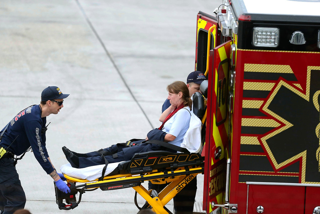 . An injured woman is loaded into an emergency vehicle at Fort Lauderdale-Hollywood International Airport after a gunman opened fire inside a terminal of the airport, killing several people and wounding others before being taken into custody, Friday, Jan. 6, 2017, in Fort Lauderdale, Fla.   (David Santiago/El Nuevo Herald via AP)