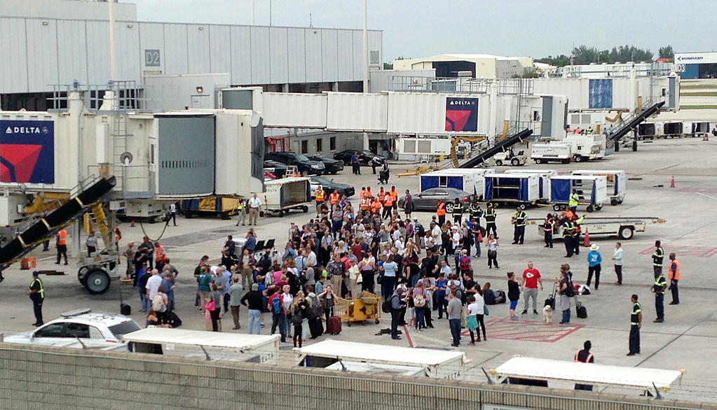 . People stand on the tarmac at the Fort Lauderdale-Hollywood International Airport after a shooter opened fire inside a terminal of the airport, killing several people and wounding others before being taken into custody, Friday, Jan. 6, 2017, in Fort Lauderdale, Fla. (AP Photo/Wilfredo Lee)