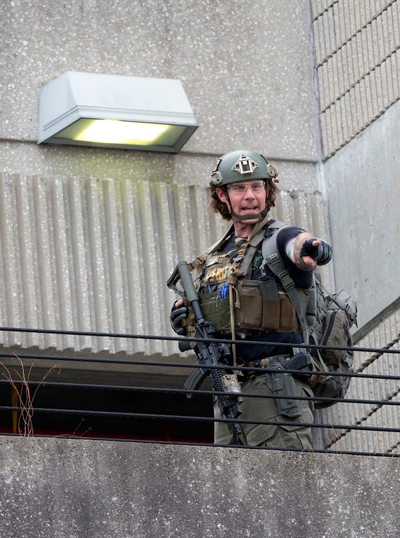 . A member of law enforcement gestures outside a garage area at Fort Lauderdale�Hollywood International Airport, Friday, Jan. 6, 2017, in Fort Lauderdale, Fla. A gunman opened fire in the baggage claim area at the airport Friday, killing several people and wounding others before being taken into custody in an attack that sent panicked passengers running out of the terminal and onto the tarmac, authorities said. (AP Photo/Wilfredo Lee)