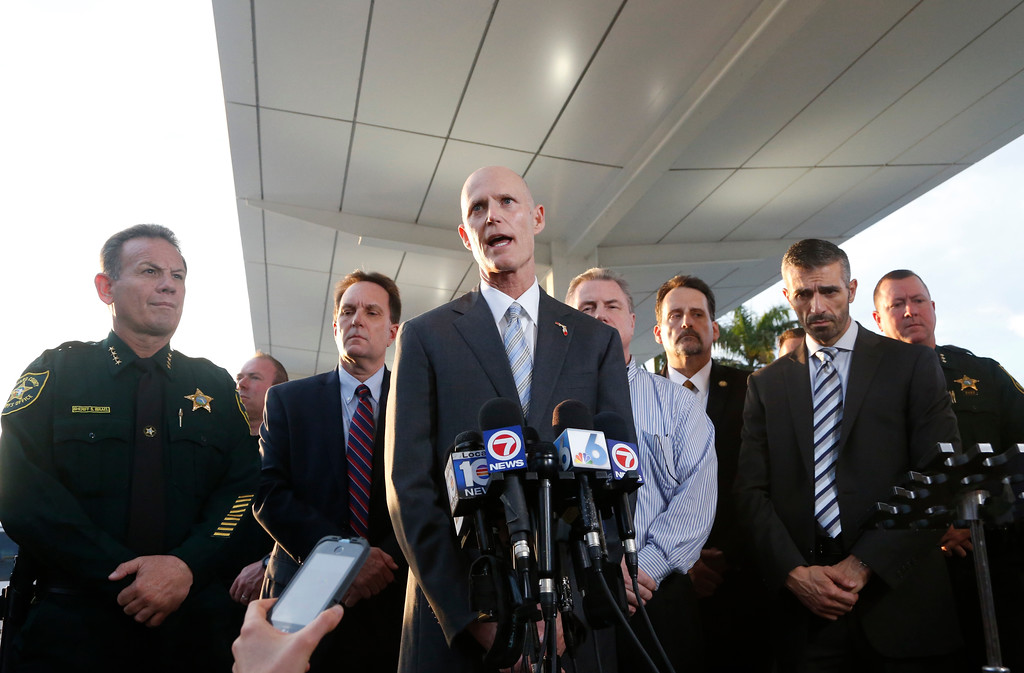 . Joined by law enforcement officials, Florida Gov. Rick Scott, center, speaks during a news conference outside Fort Lauderdale�Hollywood International Airport, Friday, Jan. 6, 2017, in Fort Lauderdale, Fla. A gunman opened fire in the baggage claim area at the airport Friday, killing several people and wounding others before being taken into custody in an attack that sent panicked passengers running out of the terminal and onto the tarmac, authorities said.  (AP Photo/Wilfredo Lee)