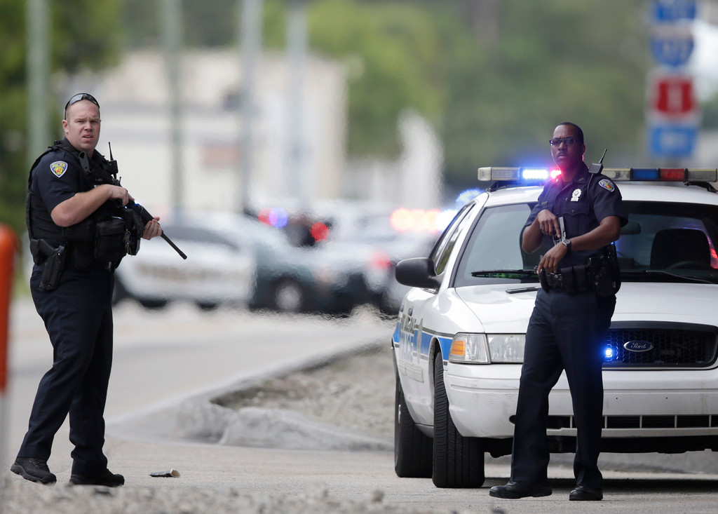 . Police officers stand on the perimeter road along the Fort Lauderdale-Hollywood International Airport after a shooter opened fire inside a terminal of the airport, killing several people and wounding others before being taken into custody, Friday, Jan. 6, 2017, in Fort Lauderdale, Fla. (AP Photo/Lynne Sladky)