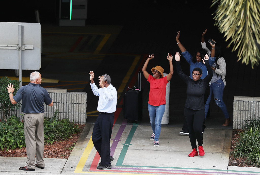 . FORT LAUDERDALE, FL - JANUARY 06: People seeking cover walk towards police with their arms raised outside the Fort Lauderdale-Hollywood International airport after a shooting took place near the baggage claim on January 6, 2017 in Fort Lauderdale, Florida. Officials are reporting that five people wear killed and eight wounded in an attack by a single gunman.   (Photo by Joe Raedle/Getty Images)