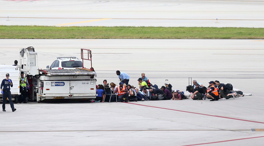 . Passengers wait on the tarmac at Fort Lauderdale-Hollywood International Airport, Friday, Jan. 6, 2017, in Fort Lauderdale, Fla.   A gunman opened fire in the baggage claim area at the airport Friday, killing several people and wounding others before being taken into custody in an attack that sent panicked passengers running out of the terminal and onto the tarmac, authorities said. (David Santiago/El Nuevo Herald via AP)