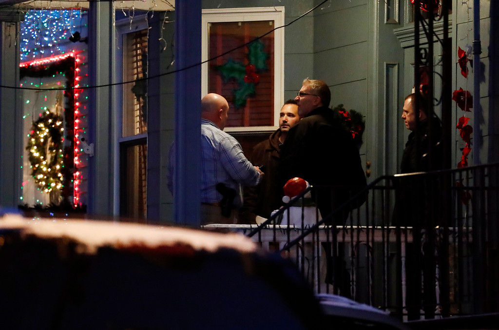 . People believed to be FBI agents are seen outside of a home believed to be inhabited by possible family members of the suspect in the shooting at the Fort Lauderdale-Hollywood International Airport, Friday, Jan. 6, 2017, in Union City, N.J. (AP Photo/Julio Cortez)