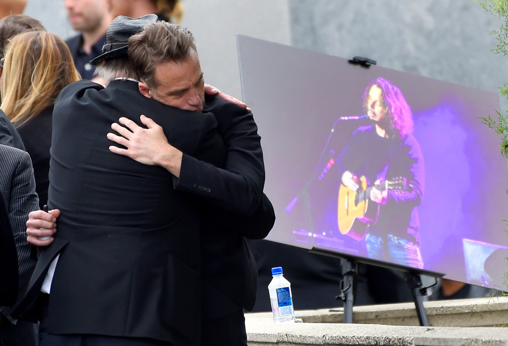 . Matt Cameron, of Soundgarden, right, hugs a guest at a funeral for Chris Cornell, pictured right, at the Hollywood Forever Cemetery on Friday, May 26, 2017, in Los Angeles. (Photo by Chris Pizzello/Invision/AP)