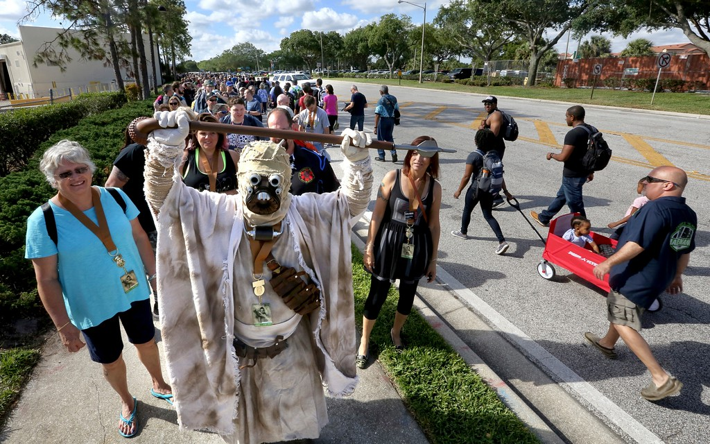". A costumed fan of the ""Star Wars\"" franchise waits in a long line outside the Orange County Center, in Orlando, Fla., to attend the 2017 Star Wars Celebration, Thursday, April 13, 2017, marking the 40th anniversary of the original 1977 Star Wars film. Thousands of fans waited for hours in the line, estimated to be more than a mile long. (Joe Burbank/Orlando Sentinel via AP)"