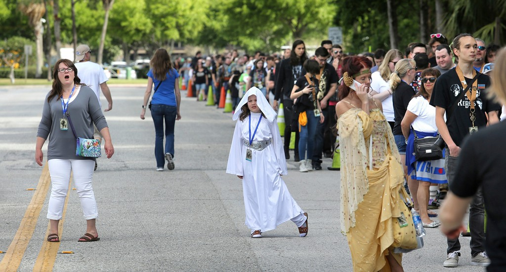 . A Star Wars fan, with her daughter dressed as Princess Leia, reacts to seeing the line outside the Orange County Center, in Orlando, Fla., at the 2017 Star Wars Celebration, Thursday, April 13, 2017, marking the 40th anniversary of the original 1977 Star Wars film. Thousands of fans waited for hours in the line, estimated to be more than a mile long, to access the convention.  (Joe Burbank/Orlando Sentinel via AP)