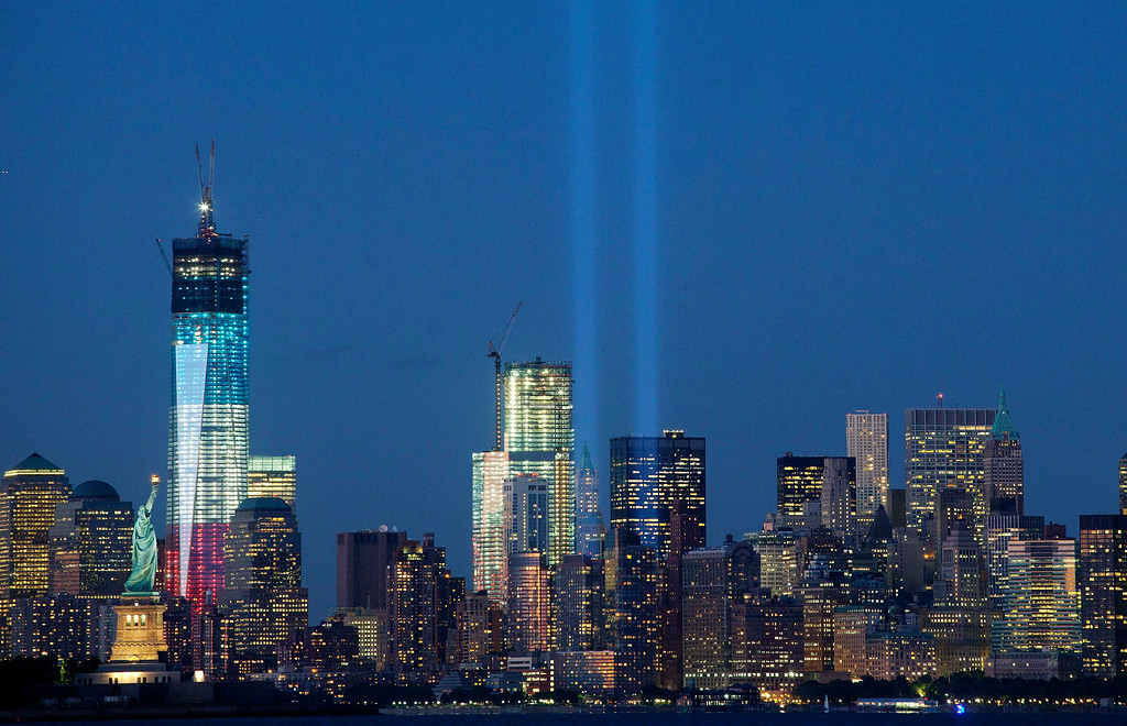 . The Tribute in Light shines above the World Trade Center in New York and the Statue of Liberty, left, Monday, Sept. 10, 2012 in this photo taken from Bayonne, N.J. (AP Photo/Mark Lennihan)