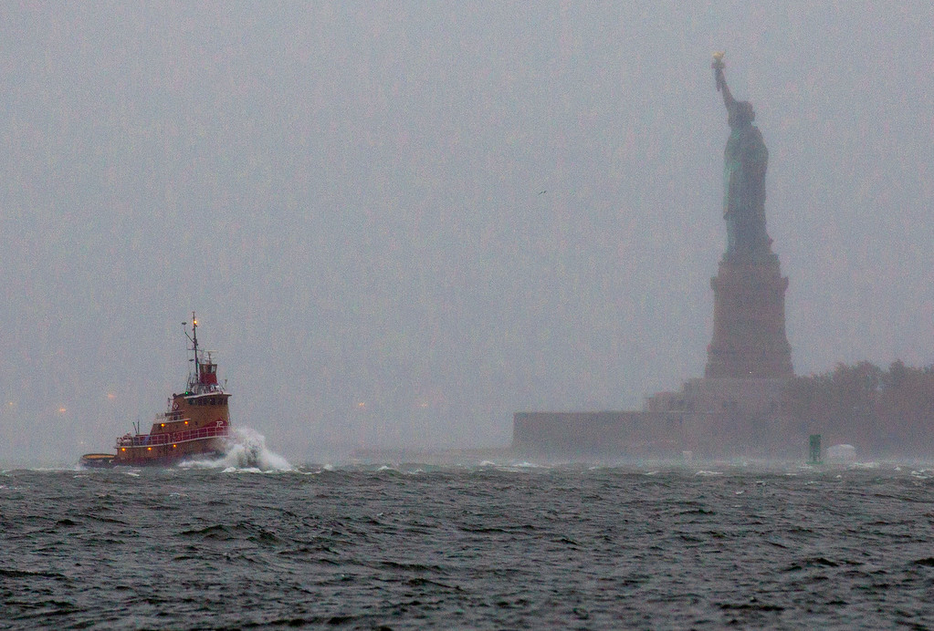 . Waves crash over the bow of a tug boat as it passes near the Statue of Liberty in New York  Monday, Oct. 29, 2012. (AP Photo/Craig Ruttle)