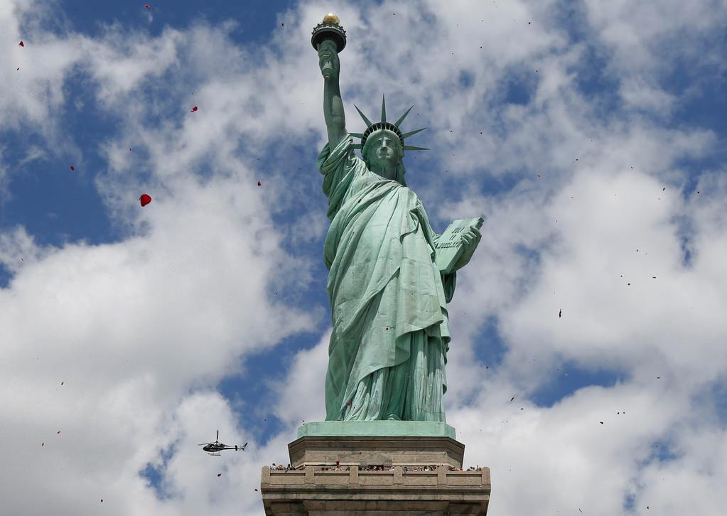 . One of three helicopters showeres 1-million rose petals on the Statue of Liberty during a ceremony commemorating the 70th anniversary of the D-Day invasion, on Liberty Island in New York Harbor, Friday, June 6, 2014. (AP Photo/Richard Drew)