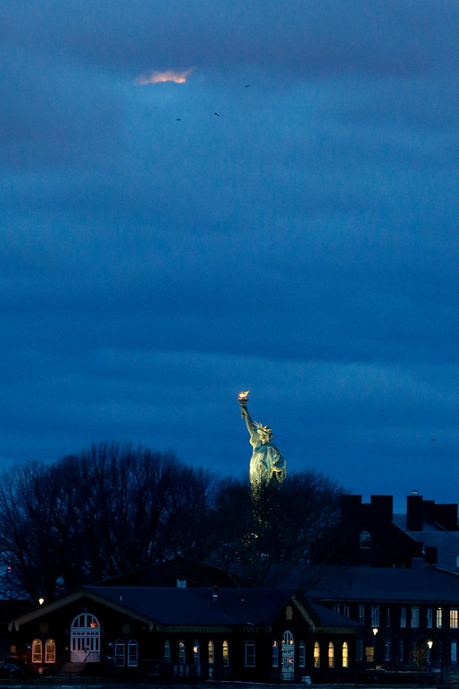 . Part of a lunar eclipse peeks through low hanging clouds over the Statue of Liberty in the early morning hours seen from Brooklyn Bridge Park, Saturday, April 4, 2015, in the Brooklyn borough of New York. (AP Photo/Julio Cortez)
