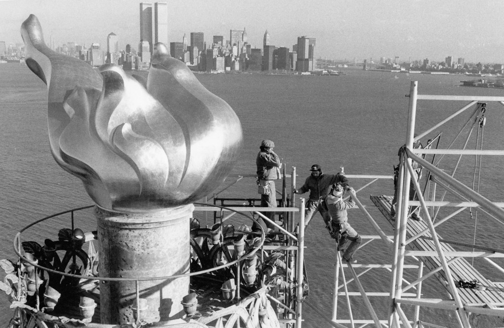. File - Workers remove 17 December 1985 scaffolding from around the torch of the Statue of Liberty, one of the world\'s most famous landmarks,  with Manhattan skyline and the twin towers of the World Trade Center in the background.        (PAUL DEMARIA/AFP/Getty Images)