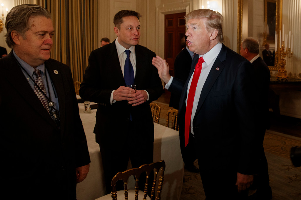 . President Donald Trump talks with Tesla and SpaceX CEO Elon Musk, center, and White House chief strategist Steve Bannon during a meeting with business leaders in the State Dining Room of the White House in Washington, Friday, Feb. 3, 2017. (AP Photo/Evan Vucci)