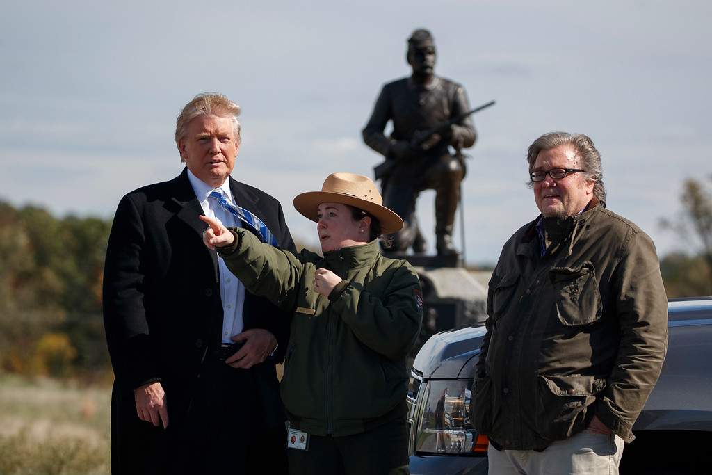 . Interpretive park ranger Caitlin Kostic, center, gives a tour near the high-water mark of the Confederacy at Gettysburg National Military Park to Republican presidential candidate Donald Trump, left, and campaign CEO Steve Bannon, Saturday, Oct. 22, 2016, in Gettysburg, Pa. (AP Photo/ Evan Vucci)