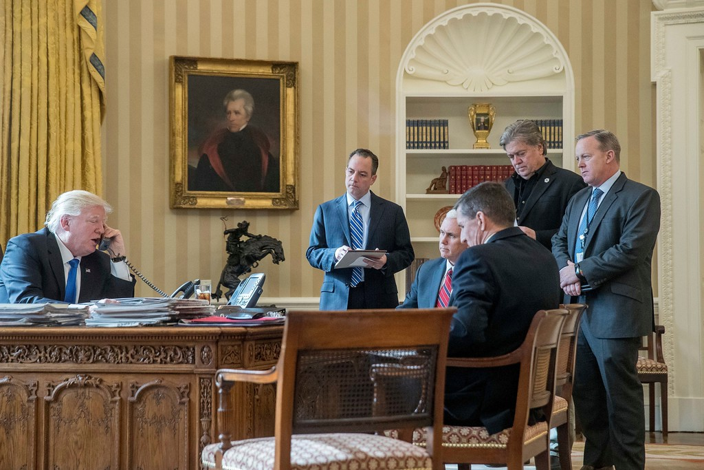 . President Donald Trump, accompanied by from second from left, Chief of Staff Reince Priebus, Vice President Mike Pence, National Security Adviser Michael Flynn, Senior Advisor Steve Bannon, and White House press secretary Sean Spicer, speaks on the phone with Russian President Vladimir Putin, Saturday, Jan. 28, 2017, in the Oval Office at the White House in Washington. (AP Photo/Andrew Harnik)