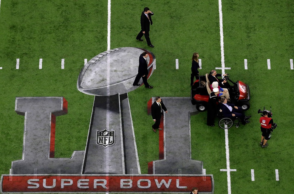 . Former President George H.W. Bush and wife, Barbara, move toward the field for a coin toss before the NFL Super Bowl 51 football game Sunday, Feb. 5, 2017, in Houston. (AP Photo/Tim Donnelly)