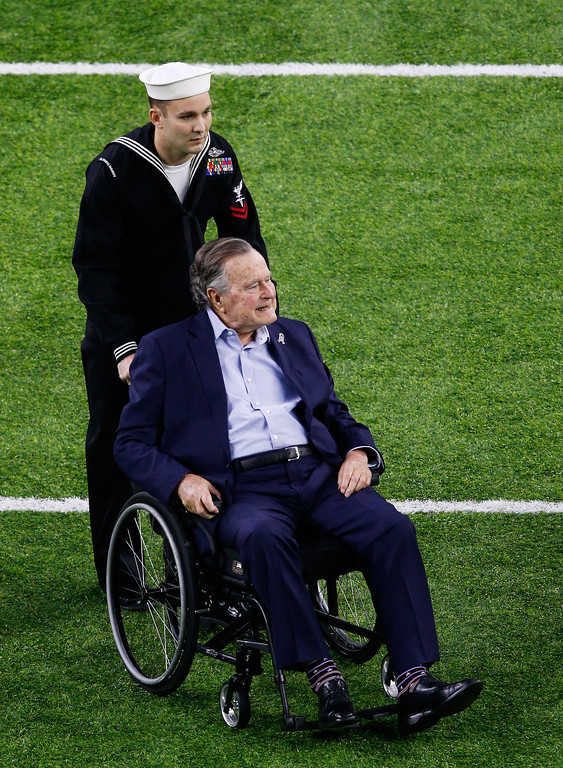 . HOUSTON, TX - FEBRUARY 05:  Former US President George H. W. Bush is helped to midfield for the coin toss prior to Super Bowl 51 between the New England Patriots and the Atlanta Falcons at NRG Stadium on February 5, 2017 in Houston, Texas.  (Photo by Bob Levey/Getty Images)